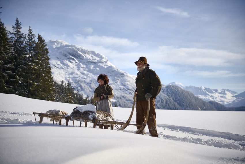 Szenenbild aus HEIDI - Im Winter sind Heidi (Anuk Steffen) und der Almöhi (Bruno Ganz) mit dem Schlitten unterwegs zur Alm- © Studiocanal