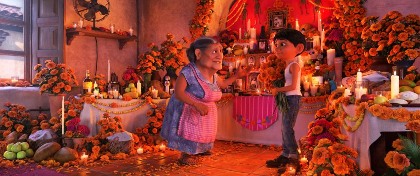 """COCO - In Disney•Pixar's""""Coco,"""" Abuelita (voice of Renée Victor) and Miguel (voice of Anthony Gonzalez) ensure that their home is adorned for Día de Muertos, including an elaborate ofrenda that holds several framed family pictures, flowers, candles, favorite foods and—because they are in the shoemaking business—shoes. """"Coco"""" opens in n U.S. theaters on Nov. 22, 2017. ©2017 Disney•Pixar. All Rights Reserved."""